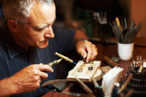 Jeweller using a blowtorch while he works on a ring